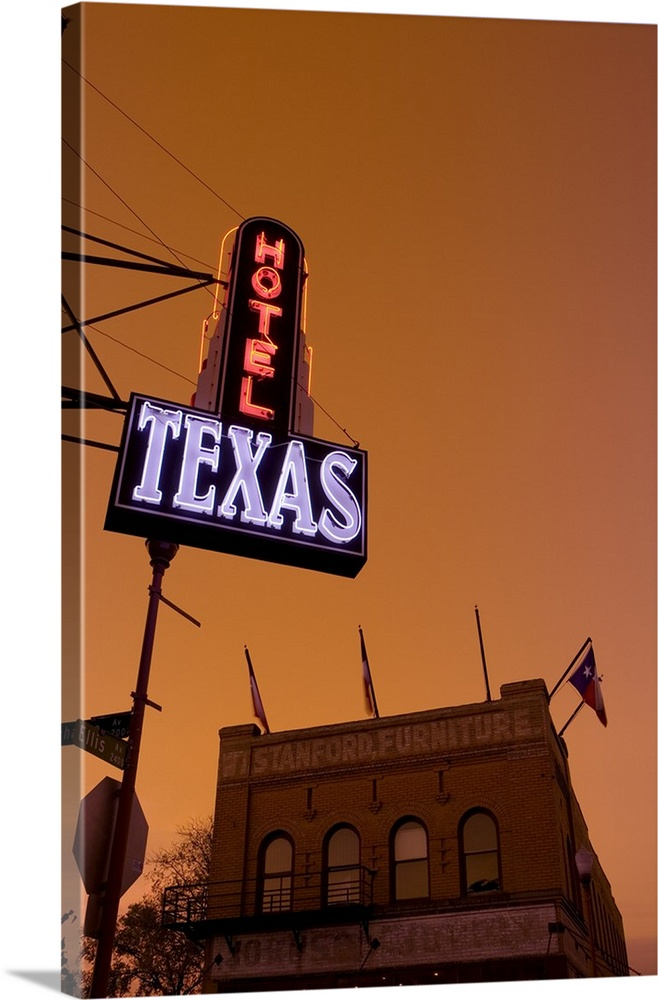 Large Gallery-Wrapped Canvas Wall Art Print 20 x 30 entitled Low angle view of a neon sign of a hotel lit up at dusk, Fort... Gallery-Wrapped Canvas entitled Low angle view of a neon sign of a hotel lit up at dusk, Fort Worth Stockyards, Fort Worth, Texas.  A hotel sign is illuminated under a sunset sky and photographed from below with a view of a furniture store building just across the street.  Multiple sizes available.  Primary colors within this image include Brown, Black, Dark Gray, Muted Blue.  Made in USA.  Satisfaction guaranteed.  Inks used are latex-based and designed to last.  Museum-quality, artist-grade canvas mounted on sturdy wooden stretcher bars 1.5 thick.  Comes ready to hang.  Canvases are stretched across a 1.5 inch thick wooden frame with easy-to-mount hanging hardware.