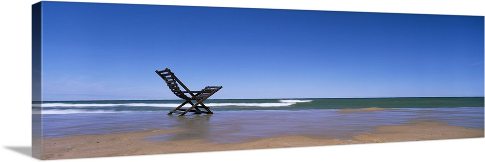Large Solid-Faced Canvas Print Wall Art Print 48 x 16 entitled Michigan, Grand Haven, Lake Michigan, Empty chair on the la... Solid-Faced Canvas Print entitled Michigan, Grand Haven, Lake Michigan, Empty chair on the lake side.  Multiple sizes available.  Primary colors within this image include Light Gray, Royal Blue, Dark Navy Blue.  Made in the USA.  All products come with a 365 day workmanship guarantee.  Archival-quality UV-resistant inks.  Featuring a proprietary design, our canvases produce the tightest corners without any bubbles, ripples, or bumps and will not warp or sag over time.  Archival inks prevent fading and preserve as much fine detail as possible with no over-saturation or color shifting.