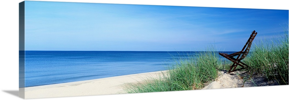 Large Solid-Faced Canvas Print Wall Art Print 48 x 16 entitled Michigan, Holland, beach chair overlooking Lake Michigan Solid-Faced Canvas Print entitled Michigan, Holland, beach chair overlooking Lake Michigan.  This wall art is a panoramic landscape photograph of a sandy beach with a chair in the dunes overlooking the lake.  Multiple sizes available.  Primary colors within this image include Black, Dark Forest Green, Pale Blue, Royal Blue.  Made in the USA.  All products come with a 365 day workmanship guarantee.  Inks used are latex-based and designed to last.  Canvas is handcrafted and made-to-order in the United States using high quality artist-grade canvas.  Archival inks prevent fading and preserve as much fine detail as possible with no over-saturation or color shifting.