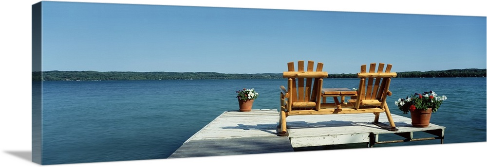 Large Solid-Faced Canvas Print Wall Art Print 48 x 16 entitled Minnesota, rear view of two Adirondack chairs on a dock Solid-Faced Canvas Print entitled Minnesota, rear view of two Adirondack chairs on a dock.  This panoramic photograph is taken from behind two chairs sitting on a dock looking out over a body of water and land in the distance.  Multiple sizes available.  Primary colors within this image include Brown, Peach, Black, Gray Blue.  Made in the USA.  Satisfaction guaranteed.  Inks used are latex-based and designed to last.  Canvas is handcrafted and made-to-order in the United States using high quality artist-grade canvas.  Archival inks prevent fading and preserve as much fine detail as possible with no over-saturation or color shifting.
