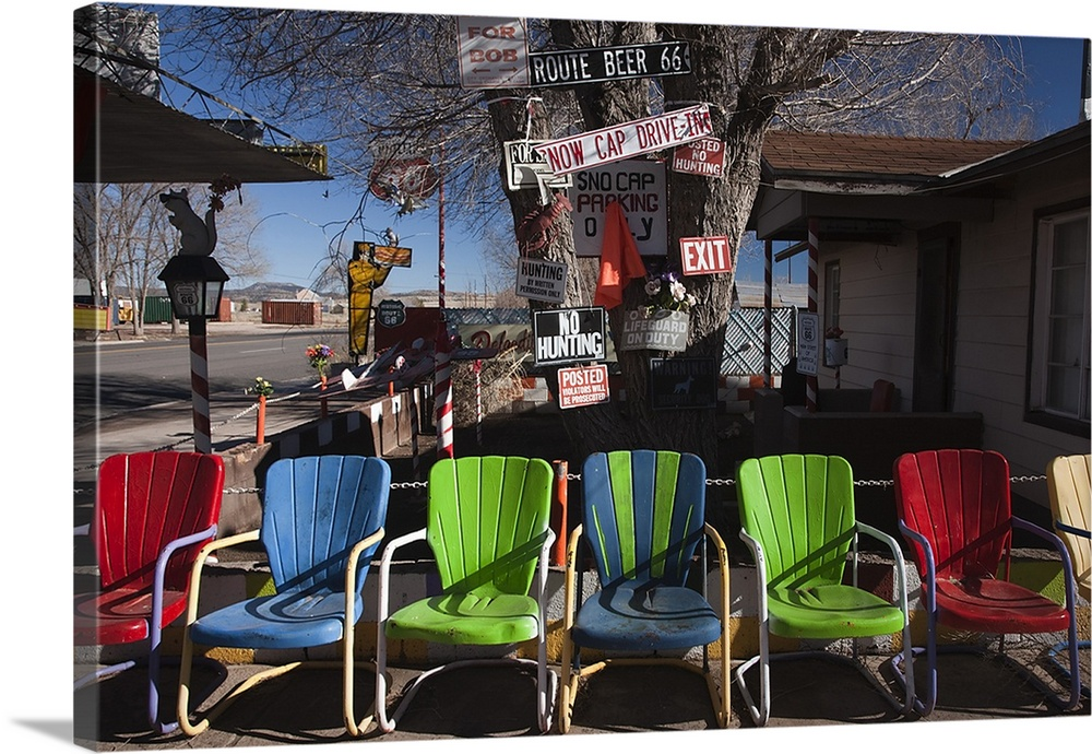 Large Solid-Faced Canvas Print Wall Art Print 30 x 20 entitled Multi colored chairs at a sidewalk cafe, Route 66, Seligman... Solid-Faced Canvas Print entitled Multi colored chairs at a sidewalk cafe, Route 66, Seligman, Yavapai County, Arizona.  Multi-colored chairs at a sidewalk cafe, Route 66, Seligman, Yavapai County, Arizona, USA.  Multiple sizes available.  Primary colors within this image include Dark Red, Forest Green, Black, White.  Made in the USA.  Satisfaction guaranteed.  Archival-quality UV-resistant inks.  Featuring a proprietary design, our canvases produce the tightest corners without any bubbles, ripples, or bumps and will not warp or sag over time.  Canvas is handcrafted and made-to-order in the United States using high quality artist-grade canvas.