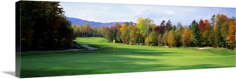 Large Solid-Faced Canvas Print Wall Art Print 48 x 16 entitled New England Golf Course New England Solid-Faced Canvas Print entitled New England Golf Course New England.  Panoramic photograph of large trees casting shadows on the green of a golf course in New England, a line of fall colored trees in the background.  Multiple sizes available.  Primary colors within this image include Dark Red, Light Yellow, Black, Pale Blue.  Made in the USA.  Satisfaction guaranteed.  Inks used are latex-based and designed to last.  Canvas depth is 1.25 and includes a finished backing with pre-installed hanging hardware.  Featuring a proprietary design, our canvases produce the tightest corners without any bubbles, ripples, or bumps and will not warp or sag over time.