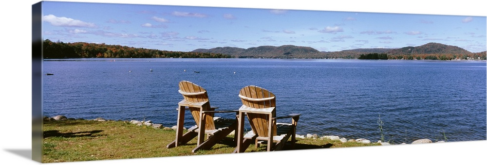 Large Solid-Faced Canvas Print Wall Art Print 48 x 16 entitled New York State, Adirondack Mountains, Fourth Lake, Chairs o... Solid-Faced Canvas Print entitled New York State, Adirondack Mountains, Fourth Lake, Chairs on a lawn.  Multiple sizes available.  Primary colors within this image include Dark Yellow, Black, Muted Blue, Pale Blue.  Made in the USA.  All products come with a 365 day workmanship guarantee.  Inks used are latex-based and designed to last.  Featuring a proprietary design, our canvases produce the tightest corners without any bubbles, ripples, or bumps and will not warp or sag over time.  Canvas is handcrafted and made-to-order in the United States using high quality artist-grade canvas.