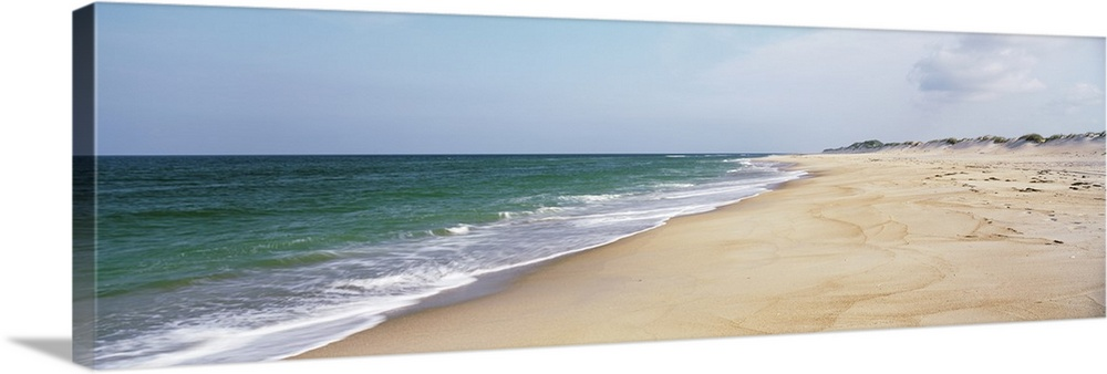 Large Solid-Faced Canvas Print Wall Art Print 48 x 16 entitled North Carolina, Cape Hatteras, Waves crashing on the beach Solid-Faced Canvas Print entitled North Carolina, Cape Hatteras, Waves crashing on the beach.  Panoramic photograph displays the Atlantic Ocean slowly coming into contact with a sandy shoreline in the Southeastern United States.  Multiple sizes available.  Primary colors within this image include Black, Gray, Silver.  Made in USA.  Satisfaction guaranteed.  Archival-quality UV-resistant inks.  Archival inks prevent fading and preserve as much fine detail as possible with no over-saturation or color shifting.  Featuring a proprietary design, our canvases produce the tightest corners without any bubbles, ripples, or bumps and will not warp or sag over time.