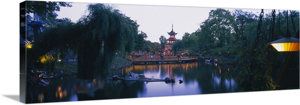 Large Solid-Faced Canvas Print Wall Art Print 48 x 16 entitled Pagoda lit up at dusk, Tivoli Gardens, Copenhagen, Denmark Solid-Faced Canvas Print entitled Pagoda lit up at dusk, Tivoli Gardens, Copenhagen, Denmark.  Multiple sizes available.  Primary colors within this image include Yellow, Dark Yellow, Dark Gray, White.  Made in USA.  All products come with a 365 day workmanship guarantee.  Archival-quality UV-resistant inks.  Canvas is handcrafted and made-to-order in the United States using high quality artist-grade canvas.  Featuring a proprietary design, our canvases produce the tightest corners without any bubbles, ripples, or bumps and will not warp or sag over time.
