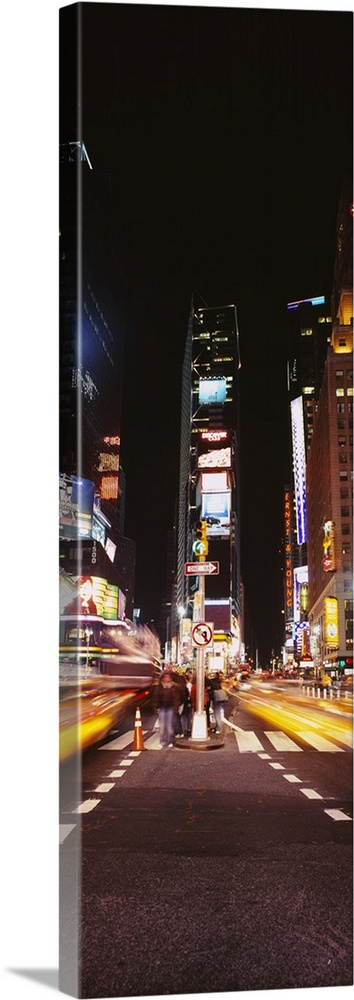 Large Gallery-Wrapped Canvas Wall Art Print 12 x 36 entitled Pedestrians waiting for crossing road, Times Square, Manhatta... Gallery-Wrapped Canvas entitled Pedestrians waiting for crossing road, Times Square, Manhattan, New York City, New York State.  This vertical time lapsed photograph shows the blur of motion created by cars driving through Time Square beneath the massive televisions.  Multiple sizes available.  Primary colors within this image include Yellow, Brown, Black, White.  Made in the USA.  Satisfaction guaranteed.  Inks used are latex-based and designed to last.  Canvas frames are built with farmed or reclaimed domestic pine or poplar wood.  Canvases are stretched across a 1.5 inch thick wooden frame with easy-to-mount hanging hardware.
