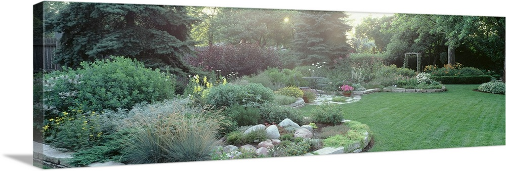 Large Solid-Faced Canvas Print Wall Art Print 48 x 16 entitled Plants in a garden, Backyard suburban garden, Illinois Solid-Faced Canvas Print entitled Plants in a garden, Backyard suburban garden, Illinois.  Multiple sizes available.  Primary colors within this image include Forest Green, Dark Gray, White.  Made in USA.  Satisfaction guaranteed.  Archival-quality UV-resistant inks.  Canvas depth is 1.25 and includes a finished backing with pre-installed hanging hardware.  Featuring a proprietary design, our canvases produce the tightest corners without any bubbles, ripples, or bumps and will not warp or sag over time.