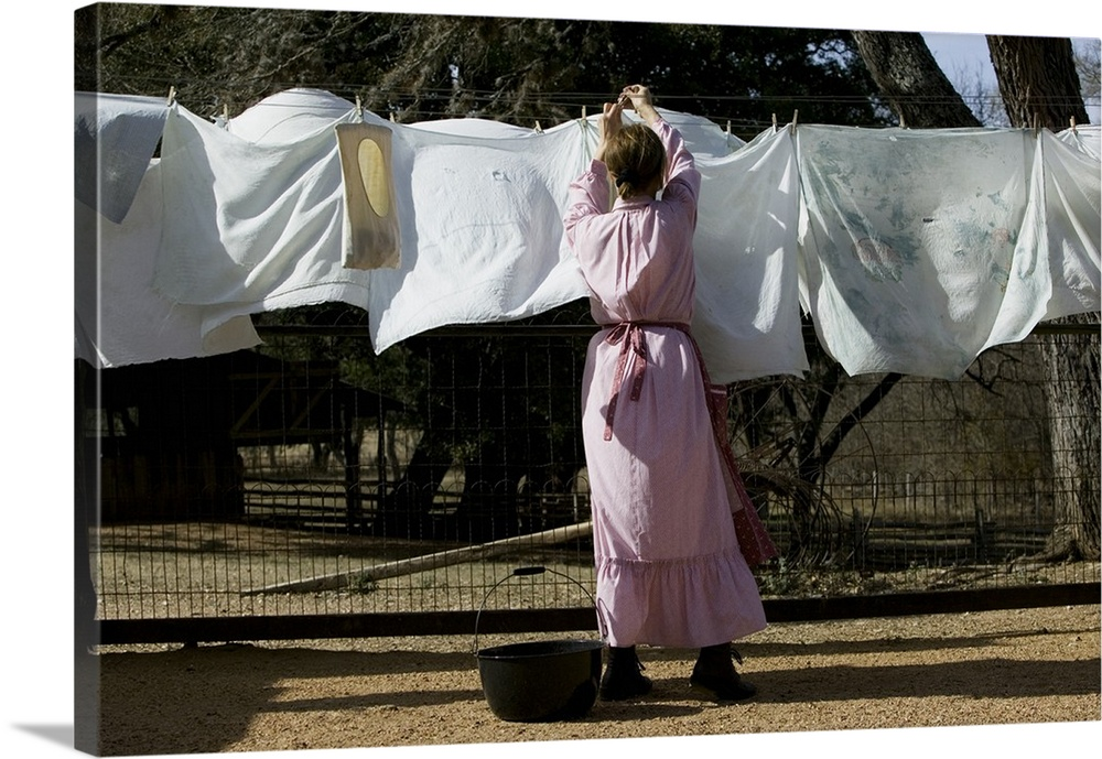 Large Gallery-Wrapped Canvas Wall Art Print 24 x 16 entitled Rear view of a woman drying clothes on a clothesline, Lyndon ... Gallery-Wrapped Canvas entitled Rear view of a woman drying clothes on a clothesline, Lyndon B. Johnson National Historical Park, Johnson City, Texas.  Multiple sizes available.  Primary colors within this image include Black, Gray, Silver.  Made in USA.  Satisfaction guaranteed.  Inks used are latex-based and designed to last.  Canvas is a 65 polyester, 35 cotton base, with two acrylic latex primer basecoats and a semi-gloss inkjet receptive topcoat.  Canvases have a UVB protection built in to protect against fading and moisture and are designed to last for over 100 years.