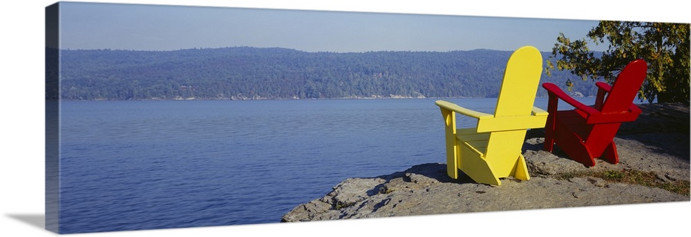 Large Solid-Faced Canvas Print Wall Art Print 48 x 16 entitled Red And Yellow Adirondack Chairs Near A Lake, Champlain Lak... Solid-Faced Canvas Print entitled Red And Yellow Adirondack Chairs Near A Lake, Champlain Lake, Vermont.  Multiple sizes available.  Primary colors within this image include Dark Red, Brown, Light Yellow, Gray Blue.  Made in USA.  Satisfaction guaranteed.  Inks used are latex-based and designed to last.  Featuring a proprietary design, our canvases produce the tightest corners without any bubbles, ripples, or bumps and will not warp or sag over time.  Canvas depth is 1.25 and includes a finished backing with pre-installed hanging hardware.