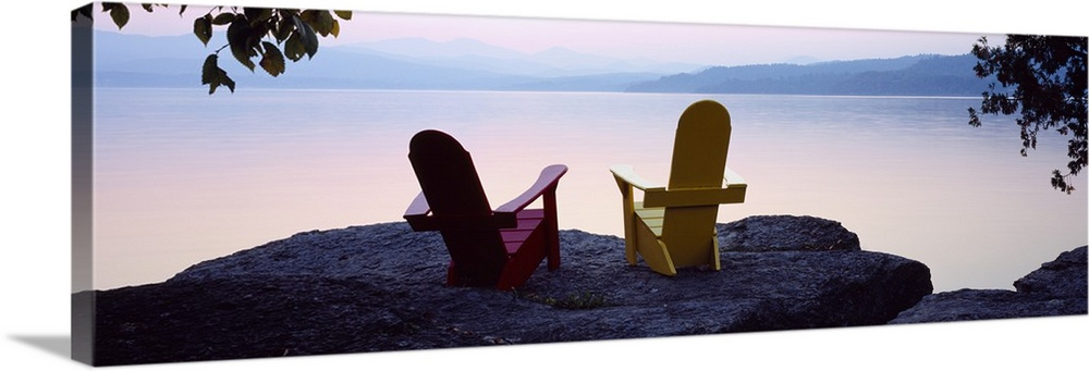 Large Solid-Faced Canvas Print Wall Art Print 48 x 16 entitled Red and Yellow Adirondack chairs on a rock near a lake, Cha... Solid-Faced Canvas Print entitled Red and Yellow Adirondack chairs on a rock near a lake, Champlain Lake, Vermont.  Horizontal photograph on a big canvas of two adirondack chairs sitting at the edge of a rocky cliff, overlooking the calm waters of Champlain Lake in Vermont.  Multiple sizes available.  Primary colors within this image include Brown, Black, Muted Blue, Pale Blue.  Made in USA.  Satisfaction guaranteed.  Archival-quality UV-resistant inks.  Canvas is handcrafted and made-to-order in the United States using high quality artist-grade canvas.  Archival inks prevent fading and preserve as much fine detail as possible with no over-saturation or color shifting.