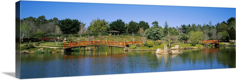 Large Solid-Faced Canvas Print Wall Art Print 48 x 16 entitled Reflection of trees and bridges in water, Japanese Gardens ... Solid-Faced Canvas Print entitled Reflection of trees and bridges in water, Japanese Gardens in Toowoomba City, Queensland, Australia.  Multiple sizes available.  Primary colors within this image include Dark Red, Dark Yellow, Sky Blue, Black.  Made in the USA.  All products come with a 365 day workmanship guarantee.  Inks used are latex-based and designed to last.  Canvas depth is 1.25 and includes a finished backing with pre-installed hanging hardware.  Featuring a proprietary design, our canvases produce the tightest corners without any bubbles, ripples, or bumps and will not warp or sag over time.