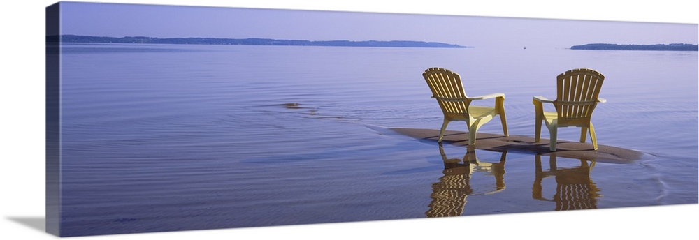 Large Solid-Faced Canvas Print Wall Art Print 48 x 16 entitled Reflection of two adirondack chairs in a lake, Lake Michiga... Solid-Faced Canvas Print entitled Reflection of two adirondack chairs in a lake, Lake Michigan, Michigan.  Panoramic photograph of two beach chairs sitting on top of sand bar with land in the far distance.  Multiple sizes available.  Primary colors within this image include Peach, Muted Blue, Dark Forest Green, Pale Blue.  Made in USA.  All products come with a 365 day workmanship guarantee.  Archival-quality UV-resistant inks.  Canvas is handcrafted and made-to-order in the United States using high quality artist-grade canvas.  Canvas depth is 1.25 and includes a finished backing with pre-installed hanging hardware.