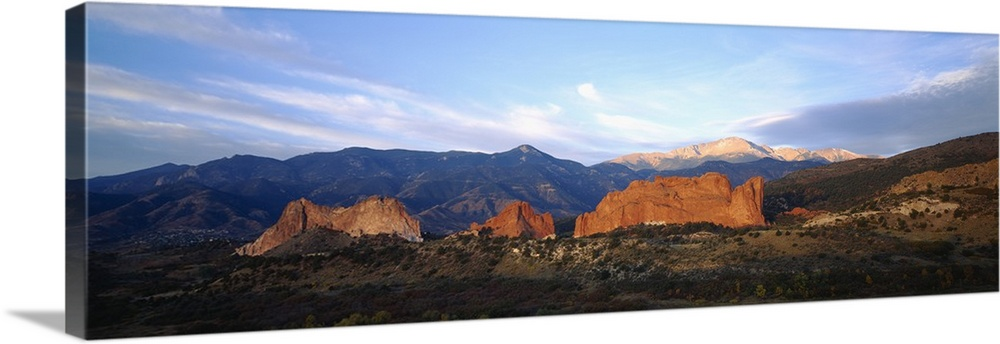 Large Solid-Faced Canvas Print Wall Art Print 48 x 16 entitled Rock formations on a landscape, Garden Of The Gods, Colorad... Solid-Faced Canvas Print entitled Rock formations on a landscape, Garden Of The Gods, Colorado Springs, Colorado.  Panoramic photograph displays a stretch of open terrain in the Western United States.  In the middle of this picture there is a row of large rock structures, while snow capped mountains are arranged across the horizon in the background.  Multiple sizes available.  Primary colors within this image include Brown, Sky Blue, Dark Gray.  Made in USA.  All products come with a 365 day workmanship guarantee.  Archival-quality UV-resistant inks.  Featuring a proprietary design, our canvases produce the tightest corners without any bubbles, ripples, or bumps and will not warp or sag over time.  Canvas is handcrafted and made-to-order in the United States using high quality artist-grade canvas.
