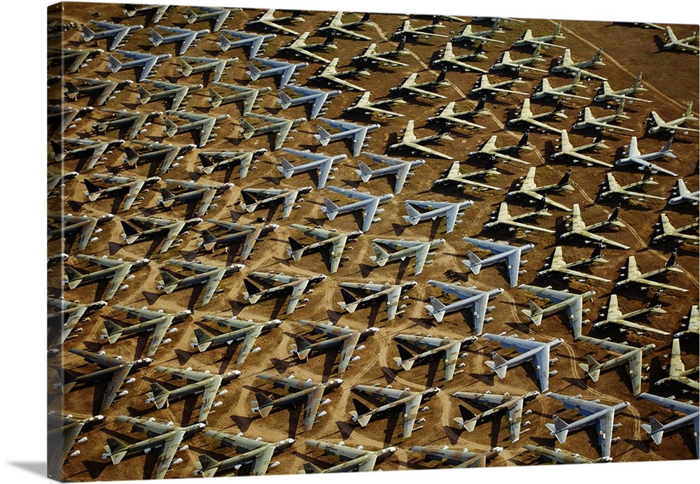 Large Solid-Faced Canvas Print Wall Art Print 30 x 20 entitled Rows of B-52s Tucson AZ Solid-Faced Canvas Print entitled Rows of B-52s Tucson AZ.  Field of retired airplanes arranged in a geometric pattern in the desert, shining in the sunlight and casting dark shadows.  Multiple sizes available.  Primary colors within this image include Peach, Dark Forest Green, Light Gray Blue.  Made in USA.  Satisfaction guaranteed.  Archival-quality UV-resistant inks.  Featuring a proprietary design, our canvases produce the tightest corners without any bubbles, ripples, or bumps and will not warp or sag over time.  Canvas is handcrafted and made-to-order in the United States using high quality artist-grade canvas.