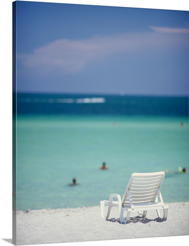 Large Solid-Faced Canvas Print Wall Art Print 24 x 30 entitled Single Beach Chair Miami Beach FL Solid-Faced Canvas Print entitled Single Beach Chair Miami Beach FL.  This vertical piece is of a single lounge chair sitting on the white sand with the ocean and sky in front of it and out of focus.  Multiple sizes available.  Primary colors within this image include Black, Gray, Muted Blue, Light Gray Blue.  Made in the USA.  All products come with a 365 day workmanship guarantee.  Inks used are latex-based and designed to last.  Canvas is handcrafted and made-to-order in the United States using high quality artist-grade canvas.  Featuring a proprietary design, our canvases produce the tightest corners without any bubbles, ripples, or bumps and will not warp or sag over time.