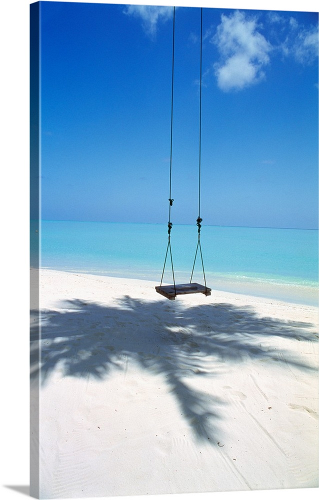 Large Solid-Faced Canvas Print Wall Art Print 20 x 30 entitled Swing on the beach above palm tree shadow Solid-Faced Canvas Print entitled Swing on the beach above palm tree shadow.  Multiple sizes available.  Primary colors within this image include Sky Blue, Black, White, Royal Blue.  Made in USA.  Satisfaction guaranteed.  Archival-quality UV-resistant inks.  Canvas depth is 1.25 and includes a finished backing with pre-installed hanging hardware.  Canvas is handcrafted and made-to-order in the United States using high quality artist-grade canvas.
