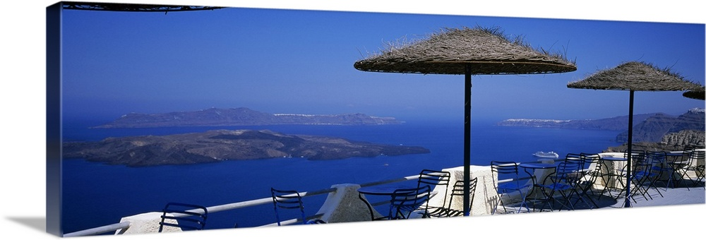 Large Solid-Faced Canvas Print Wall Art Print 48 x 16 entitled Table and chairs on a balcony, Santo Winery, Fira, Oia, San... Solid-Faced Canvas Print entitled Table and chairs on a balcony, Santo Winery, Fira, Oia, Santorini, Greece.  Multiple sizes available.  Primary colors within this image include Dark Blue, Black, Light Gray, Royal Blue.  Made in USA.  Satisfaction guaranteed.  Inks used are latex-based and designed to last.  Archival inks prevent fading and preserve as much fine detail as possible with no over-saturation or color shifting.  Featuring a proprietary design, our canvases produce the tightest corners without any bubbles, ripples, or bumps and will not warp or sag over time.