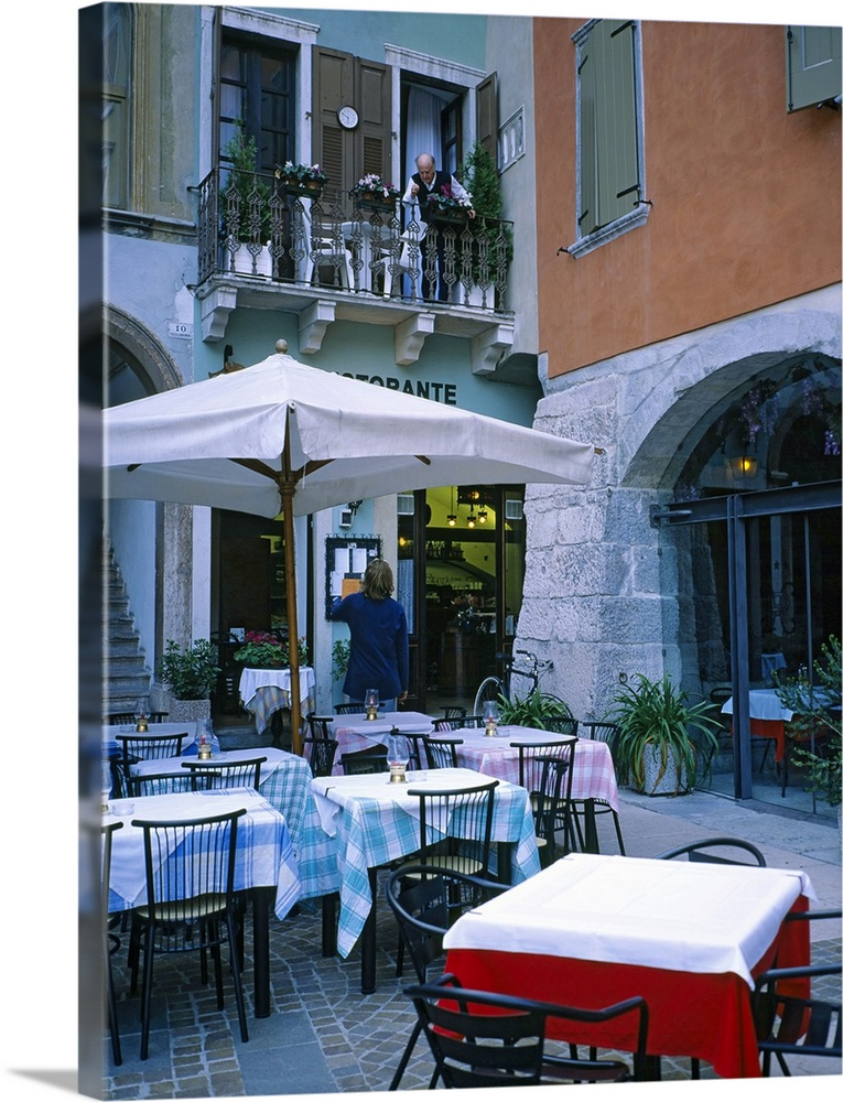 Large Solid-Faced Canvas Print Wall Art Print 30 x 40 entitled Tables and chairs at a sidewalk cafe, Lake Garda, Italy Solid-Faced Canvas Print entitled Tables and chairs at a sidewalk cafe, Lake Garda, Italy.  Vertical panoramic photograph outside eatery next to street shops at dusk.  Multiple sizes available.  Primary colors within this image include Dark Red, Gray, White, Dark Navy Blue.  Made in USA.  Satisfaction guaranteed.  Archival-quality UV-resistant inks.  Canvas is handcrafted and made-to-order in the United States using high quality artist-grade canvas.  Featuring a proprietary design, our canvases produce the tightest corners without any bubbles, ripples, or bumps and will not warp or sag over time.