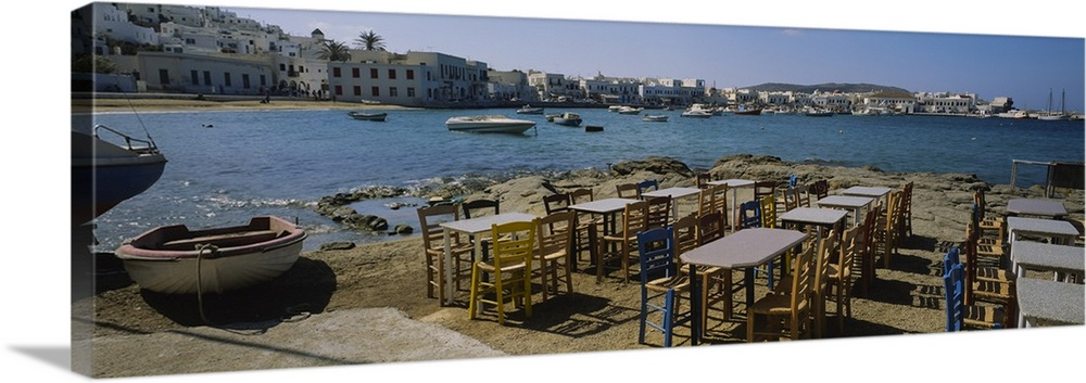 Large Solid-Faced Canvas Print Wall Art Print 48 x 16 entitled Tables and chairs in a cafe, Greece Solid-Faced Canvas Print entitled Tables and chairs in a cafe, Greece.  Multiple sizes available.  Primary colors within this image include Brown, Black, Light Gray Blue.  Made in USA.  Satisfaction guaranteed.  Archival-quality UV-resistant inks.  Canvas is handcrafted and made-to-order in the United States using high quality artist-grade canvas.  Canvas depth is 1.25 and includes a finished backing with pre-installed hanging hardware.