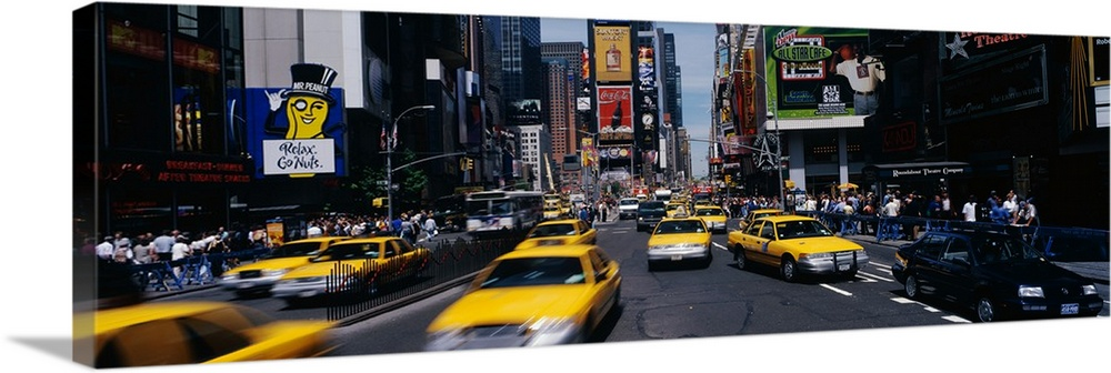 Large Solid-Faced Canvas Print Wall Art Print 48 x 16 entitled Times Square New York NY Solid-Faced Canvas Print entitled Times Square New York NY.  Wide angle photograph of many taxi cabs rushing through the streets, surrounded by the large advertising signs of Times Square in New York City, during the day.  Multiple sizes available.  Primary colors within this image include Yellow, Brown, Black, Pale Blue.  Made in the USA.  All products come with a 365 day workmanship guarantee.  Inks used are latex-based and designed to last.  Canvas depth is 1.25 and includes a finished backing with pre-installed hanging hardware.  Canvas is handcrafted and made-to-order in the United States using high quality artist-grade canvas.