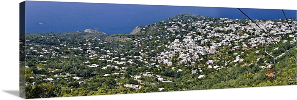 Large Solid-Faced Canvas Print Wall Art Print 48 x 16 entitled Town viewed from a chair lift Anacapri Capri Naples Campani... Solid-Faced Canvas Print entitled Town viewed from a chair lift Anacapri Capri Naples Campania Italy.  Multiple sizes available.  Primary colors within this image include Black, White, Dark Forest Green, Royal Blue.  Made in the USA.  All products come with a 365 day workmanship guarantee.  Inks used are latex-based and designed to last.  Archival inks prevent fading and preserve as much fine detail as possible with no over-saturation or color shifting.  Featuring a proprietary design, our canvases produce the tightest corners without any bubbles, ripples, or bumps and will not warp or sag over time.