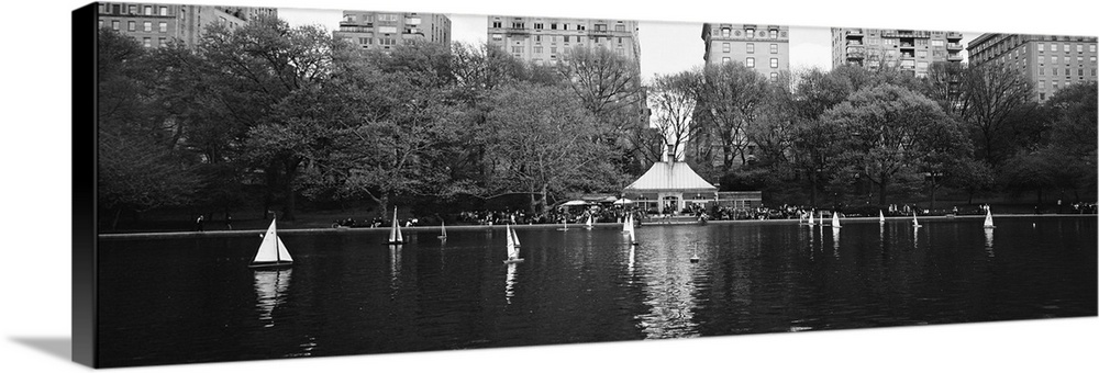 Large Solid-Faced Canvas Print Wall Art Print 48 x 16 entitled Toy boats floating on water, Central Park, Manhattan, New Y... Solid-Faced Canvas Print entitled Toy boats floating on water, Central Park, Manhattan, New York City.  Multiple sizes available.  Primary colors within this image include Dark Gray, Light Gray.  Made in USA.  All products come with a 365 day workmanship guarantee.  Archival-quality UV-resistant inks.  Featuring a proprietary design, our canvases produce the tightest corners without any bubbles, ripples, or bumps and will not warp or sag over time.  Canvas depth is 1.25 and includes a finished backing with pre-installed hanging hardware.