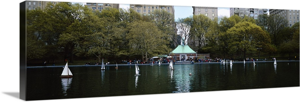 Large Solid-Faced Canvas Print Wall Art Print 48 x 16 entitled Toy boats floating on water, Central Park, Manhattan, New Y... Solid-Faced Canvas Print entitled Toy boats floating on water, Central Park, Manhattan, New York City, New York State.  Multiple sizes available.  Primary colors within this image include Gray, White, Dark Forest Green, Dark Navy Blue.  Made in USA.  All products come with a 365 day workmanship guarantee.  Archival-quality UV-resistant inks.  Canvas is handcrafted and made-to-order in the United States using high quality artist-grade canvas.  Archival inks prevent fading and preserve as much fine detail as possible with no over-saturation or color shifting.