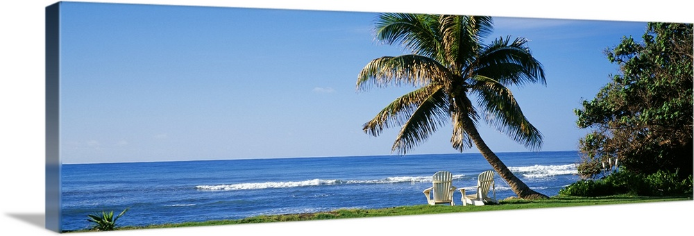 Large Solid-Faced Canvas Print Wall Art Print 48 x 16 entitled Two adirondack chairs near a palm tree, Oahu, Hawaii Solid-Faced Canvas Print entitled Two adirondack chairs near a palm tree, Oahu, Hawaii.  This is a panoramic photograph of a grassy lawn that grows up the shoreline where two lounge chairs face the sea in the shade of a tropical tree.  Multiple sizes available.  Primary colors within this image include Peach, White, Dark Forest Green, Royal Blue.  Made in the USA.  Satisfaction guaranteed.  Archival-quality UV-resistant inks.  Canvas is handcrafted and made-to-order in the United States using high quality artist-grade canvas.  Canvas depth is 1.25 and includes a finished backing with pre-installed hanging hardware.