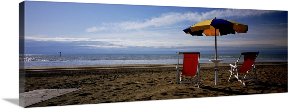 Large Gallery-Wrapped Canvas Wall Art Print 36 x 13 entitled Two empty chairs under a beach umbrella, Lignano Sabbiadoro, ... Gallery-Wrapped Canvas entitled Two empty chairs under a beach umbrella, Lignano Sabbiadoro, Italy.  Multiple sizes available.  Primary colors within this image include Dark Red, Black, Gray, Light Gray Blue.  Made in USA.  All products come with a 365 day workmanship guarantee.  Archival-quality UV-resistant inks.  Canvas is designed to prevent fading.  Canvas frames are built with farmed or reclaimed domestic pine or poplar wood.