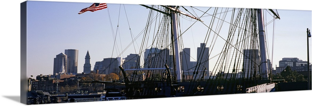 Large Solid-Faced Canvas Print Wall Art Print 60 x 20 entitled Warship at a harbor in front of skyscrapers, USS Constituti... Solid-Faced Canvas Print entitled Warship at a harbor in front of skyscrapers, USS Constitution, Freedom Trail, Boston, Massachusetts.  Multiple sizes available.  Primary colors within this image include Brown, Black, Gray, Pale Blue.  Made in USA.  All products come with a 365 day workmanship guarantee.  Archival-quality UV-resistant inks.  Featuring a proprietary design, our canvases produce the tightest corners without any bubbles, ripples, or bumps and will not warp or sag over time.  Canvas is handcrafted and made-to-order in the United States using high quality artist-grade canvas.