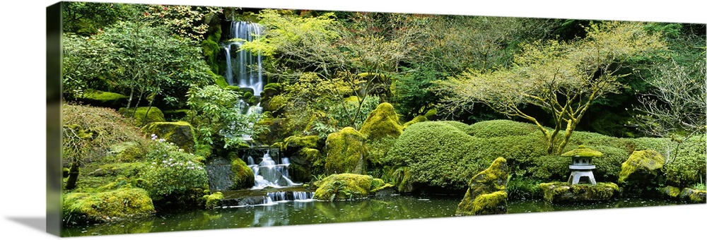 Large Solid-Faced Canvas Print Wall Art Print 48 x 16 entitled Waterfall in a garden, Japanese Garden, Washington Park, Po... Solid-Faced Canvas Print entitled Waterfall in a garden, Japanese Garden, Washington Park, Portland, Oregon.  Wide angle photograph taken of a small waterfall inside a Japanese garden. Its surrounded by lush green foliage.  Multiple sizes available.  Primary colors within this image include Forest Green, Light Yellow, Black, White.  Made in USA.  Satisfaction guaranteed.  Inks used are latex-based and designed to last.  Canvas depth is 1.25 and includes a finished backing with pre-installed hanging hardware.  Canvas is handcrafted and made-to-order in the United States using high quality artist-grade canvas.