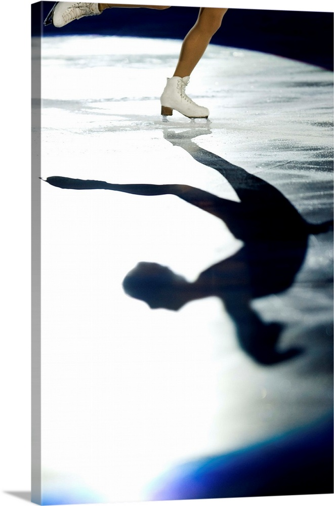 Large Solid-Faced Canvas Print Wall Art Print 20 x 30 entitled Shadow of female figure skater in action Solid-Faced Canvas Print entitled Shadow of female figure skater in action.  Multiple sizes available.  Primary colors within this image include Brown, Black, White, Royal Blue.  Made in USA.  All products come with a 365 day workmanship guarantee.  Inks used are latex-based and designed to last.  Featuring a proprietary design, our canvases produce the tightest corners without any bubbles, ripples, or bumps and will not warp or sag over time.  Canvas depth is 1.25 and includes a finished backing with pre-installed hanging hardware.