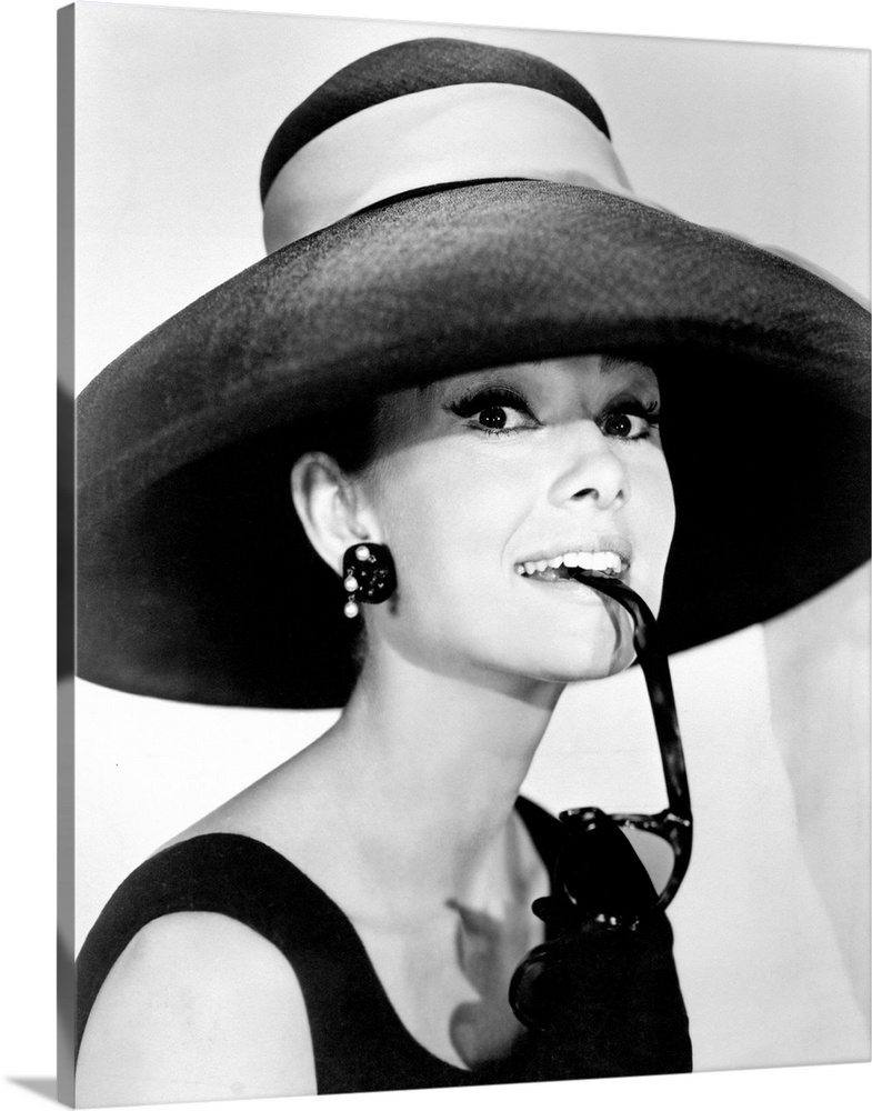 Large Gallery-Wrapped Canvas Wall Art Print 16 x 20 entitled Audrey Hepburn B Gallery-Wrapped Canvas entitled Audrey Hepburn B.  Large photograph of Audrey Hepburn in a giant sun hat holding sunglasses in her mouth as she glances at the camera in a black dress.  Multiple sizes available.  Primary colors within this image include Dark Gray Silver.  Made in the USA.  All products come with a 365 day workmanship guarantee.  Inks used are latex-based and designed to last.  Canvases are stretched across a 1.5 inch thick wooden frame with easy-to-mount hanging hardware.  Museum-quality artist-grade canvas mounted on sturdy wooden stretcher bars 1.5 thick.  Comes ready to hang.