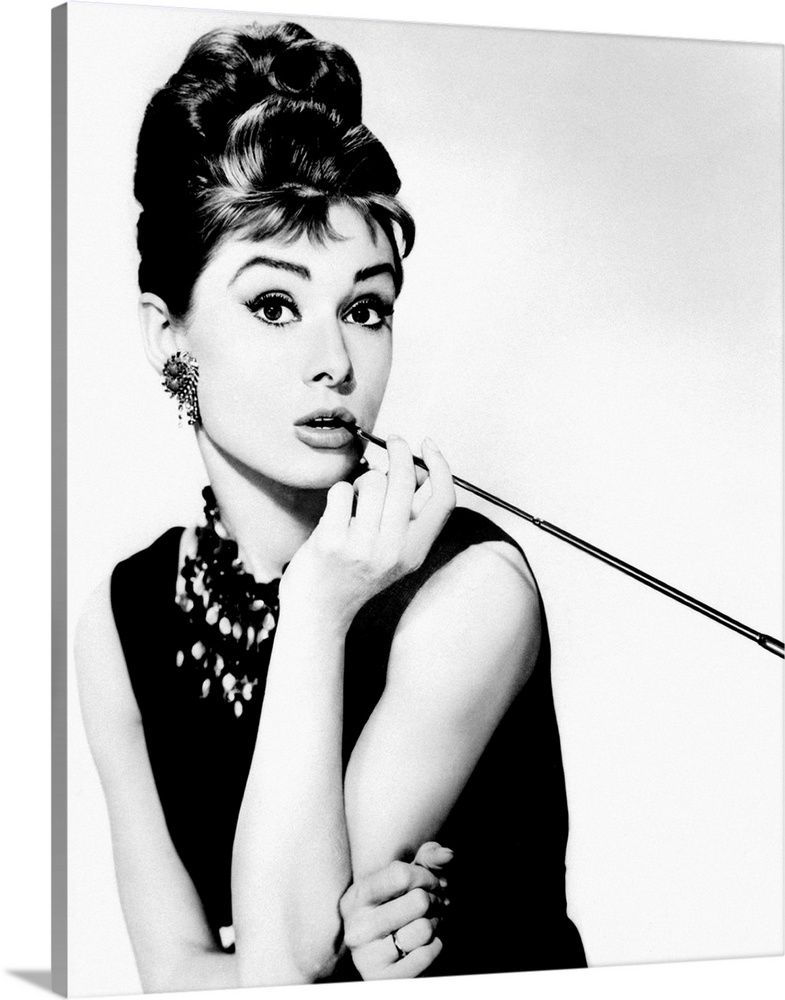 Large Gallery-Wrapped Canvas Wall Art Print 16 x 20 entitled Audrey Hepburn Breakfast Tiffanys 16 Gallery-Wrapped Canvas entitled Audrey Hepburn Breakfast Tiffanys 16.  This wall art is a portrait photograph of the Hollywood Icon character Holly Golightly in her signature black dress, jewelry, cigarette holder, and wing tip eye liner.  Multiple sizes available.  Primary colors within this image include Black, Gray, White.  Made in USA.  Satisfaction guaranteed.  Archival-quality UV-resistant inks.  Canvases have a UVB protection built in to protect against fading and moisture and are designed to last for over 100 years.  Canvas frames are built with farmed or reclaimed domestic pine or poplar wood.