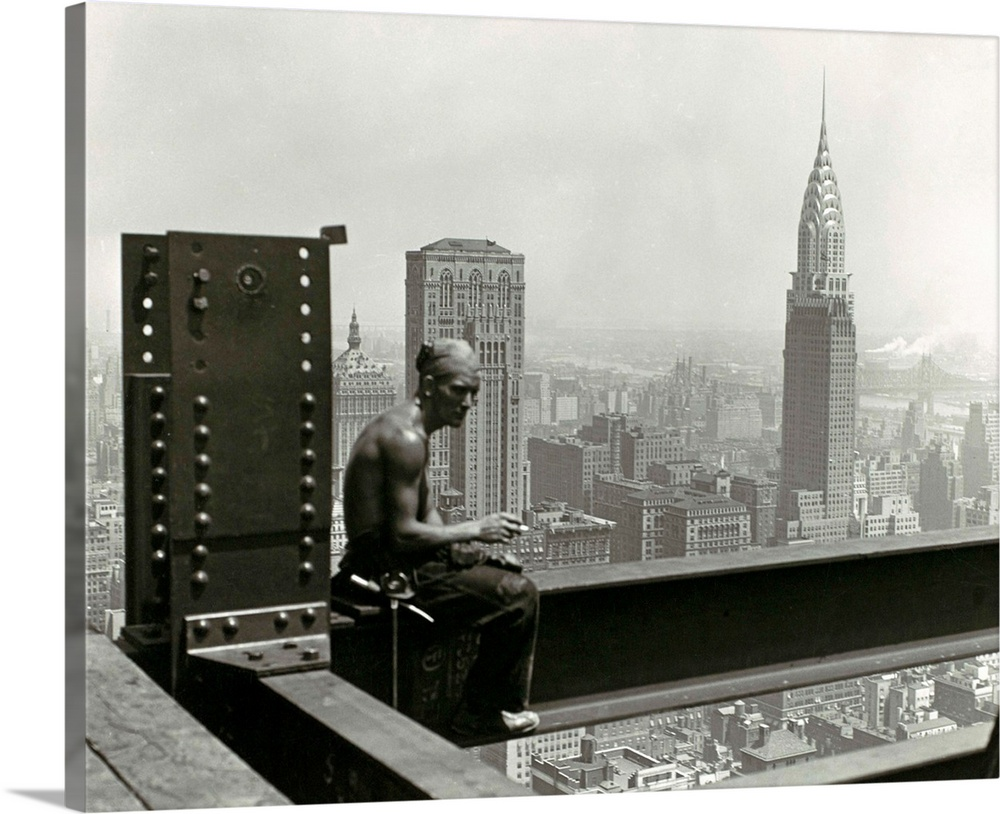 Large Solid-Faced Canvas Print Wall Art Print 30 x 24 entitled Empire State Building Solid-Faced Canvas Print entitled Empire State Building.  Hine took to great heights for this well-known photograph of a construction worker on the Empire State Building taking a break to enjoy a cigarette. Hines photograph juxtaposes the ordinary a short break from work with the extraordinary the awe-inspiring view of the city. The recently completed Chrysler Building, whose height the Empire State Building eclipsed, appears prominently amid the haze in the middle distance as if already relegated to history.  Multiple sizes available.  Primary colors within this image include Dark Gray, White.  Made in USA.  All products come with a 365 day workmanship guarantee.  Archival-quality UV-resistant inks.  Canvas depth is 1.25 and includes a finished backing with pre-installed hanging hardware.  Featuring a proprietary design, our canvases produce the tightest corners without any bubbles, ripples, or bumps and will not warp or sag over time.