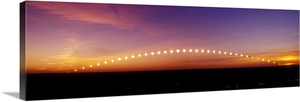Large Solid-Faced Canvas Print Wall Art Print 48 x 16 entitled Time-lapse image of a suntrail Solid-Faced Canvas Print entitled Time-lapse image of a suntrail.  Time-lapse image of a suntrail. Time-lapse exposure showing the path of the sun as it rises from below the horizon and then sets again. The sun does not rise vertically, but at an angle. The observed angle becomes shallower the further an observer is from the Earths equator. In extreme northern and southern latitudes the sun only rises a short distance above the horizon in winter, as seen here. This image is obtained by repeated exposure of the photographic film or sensor over a number of hours.  Multiple sizes available.  Primary colors within this image include Yellow, Brown, Peach, Black.  Made in the USA.  Satisfaction guaranteed.  Inks used are latex-based and designed to last.  Canvas is handcrafted and made-to-order in the United States using high quality artist-grade canvas.  Canvas depth is 1.25 and includes a finished backing with pre-installed hanging hardware.