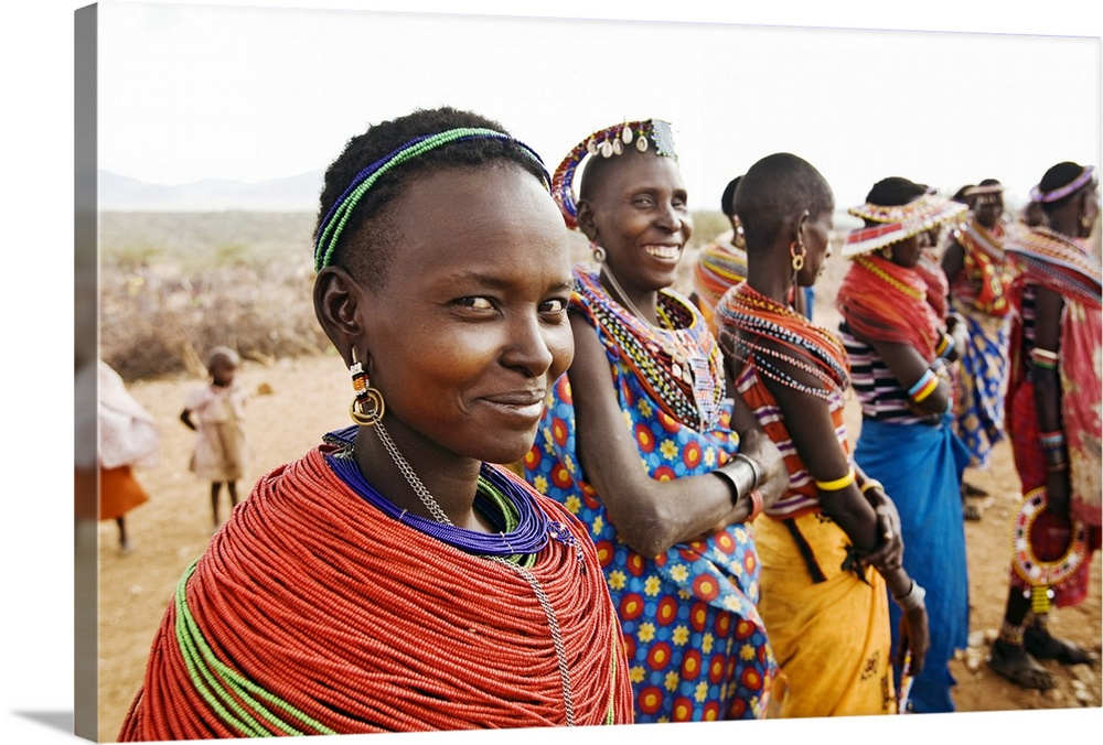 Large Gallery-Wrapped Canvas Wall Art Print 24 x 16 entitled African Samburu Tribal Pride Gallery-Wrapped Canvas entitled African Samburu Tribal Pride.  Oversized landscape photograph of the African Samburu Tribe forming a line and dressed in brightly colored garments.  Two women in the foreground smile at the camera in front of a vast desert landscape.  Multiple sizes available.  Primary colors within this image include Orange Dark Red Brown Peach.  Made in USA.  Satisfaction guaranteed.  Inks used are latex-based and designed to last.  Canvas frames are built with farmed or reclaimed domestic pine or poplar wood.  Canvas is designed to prevent fading.