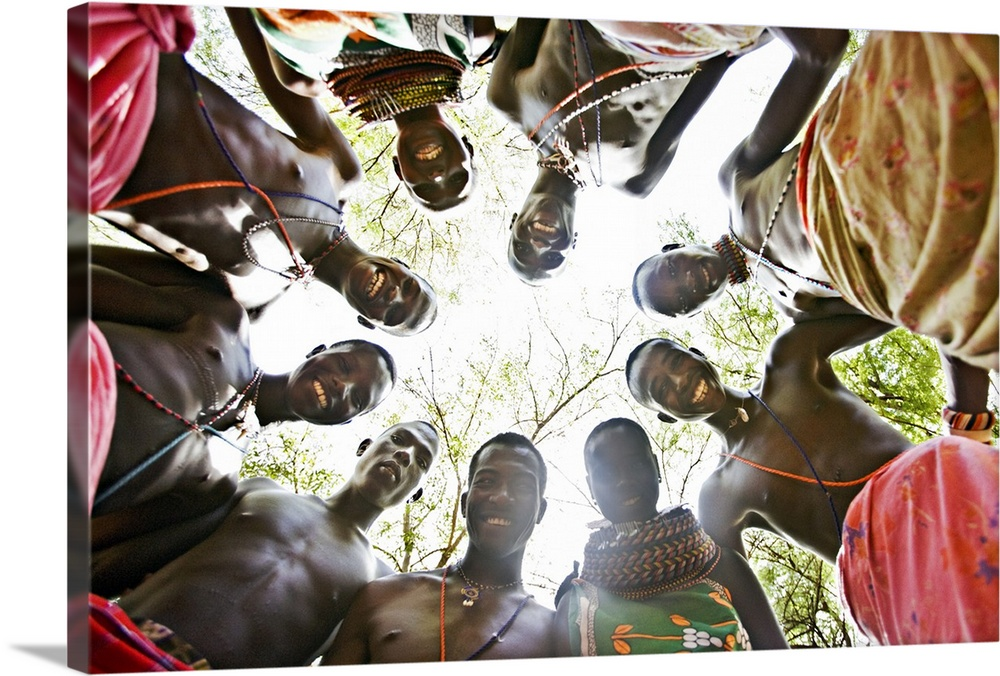 Large Gallery-Wrapped Canvas Wall Art Print 24 x 16 entitled African Tribal Smile Gallery-Wrapped Canvas entitled African Tribal Smile.  Photograph of natives in a circle looking down at camera with forest as back drop.  Multiple sizes available.  Primary colors within this image include Dark Red Black Gray White.  Made in USA.  Satisfaction guaranteed.  Archival-quality UV-resistant inks.  Canvas frames are built with farmed or reclaimed domestic pine or poplar wood.  Canvases are stretched across a 1.5 inch thick wooden frame with easy-to-mount hanging hardware.