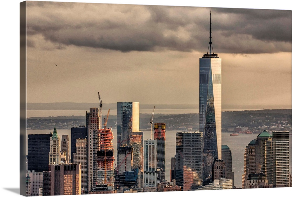 Large Solid-Faced Canvas Print Wall Art Print 36 x 24 entitled High view of Freedom One and downtown New York City Solid-Faced Canvas Print entitled High view of Freedom One and downtown New York City.  High view of Freedom One and downtown New York City.  Multiple sizes available.  Primary colors within this image include Peach, Black, Gray.  Made in the USA.  All products come with a 365 day workmanship guarantee.  Inks used are latex-based and designed to last.  Canvas depth is 1.25 and includes a finished backing with pre-installed hanging hardware.  Canvas is handcrafted and made-to-order in the United States using high quality artist-grade canvas.