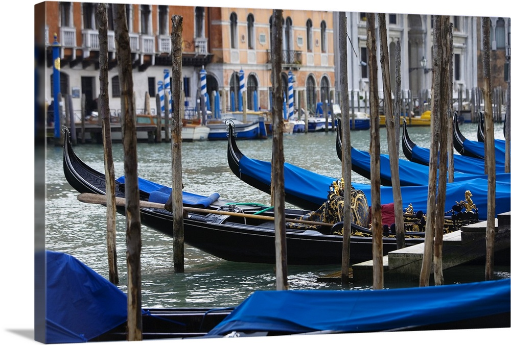 Large Gallery-Wrapped Canvas Wall Art Print 24 x 16 entitled Venice Gondola Gallery-Wrapped Canvas entitled Venice Gondola.  Photograph taken of a river in Venice that is lined with gondola boats that are tied up and have been covered with blue cloth to protect them from the weather elements.  Multiple sizes available.  Primary colors within this image include Brown, Dark Blue, Light Gray, Dark Navy Blue.  Made in the USA.  Satisfaction guaranteed.  Inks used are latex-based and designed to last.  Canvas is acid-free and 20 millimeters thick.  Canvases have a UVB protection built in to protect against fading and moisture and are designed to last for over 100 years.