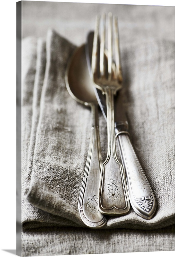 Large Solid-Faced Canvas Print Wall Art Print 20 x 30 entitled Old silver cutlery on a linen cloth Solid-Faced Canvas Print entitled Old silver cutlery on a linen cloth.  Multiple sizes available.  Primary colors within this image include Black, Silver.  Made in USA.  All products come with a 365 day workmanship guarantee.  Archival-quality UV-resistant inks.  Archival inks prevent fading and preserve as much fine detail as possible with no over-saturation or color shifting.  Canvas is handcrafted and made-to-order in the United States using high quality artist-grade canvas.