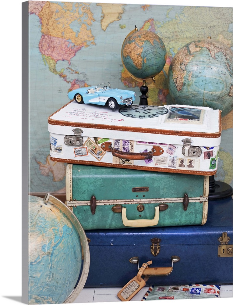 Large Solid-Faced Canvas Print Wall Art Print 30 x 40 entitled Stack of vintage suitcases, tin toy car and globes in front... Solid-Faced Canvas Print entitled Stack of vintage suitcases, tin toy car and globes in front of a map.  Multiple sizes available.  Primary colors within this image include Silver, Dark Forest Green, Dark Navy Blue.  Made in USA.  All products come with a 365 day workmanship guarantee.  Inks used are latex-based and designed to last.  Featuring a proprietary design, our canvases produce the tightest corners without any bubbles, ripples, or bumps and will not warp or sag over time.  Canvas is handcrafted and made-to-order in the United States using high quality artist-grade canvas.