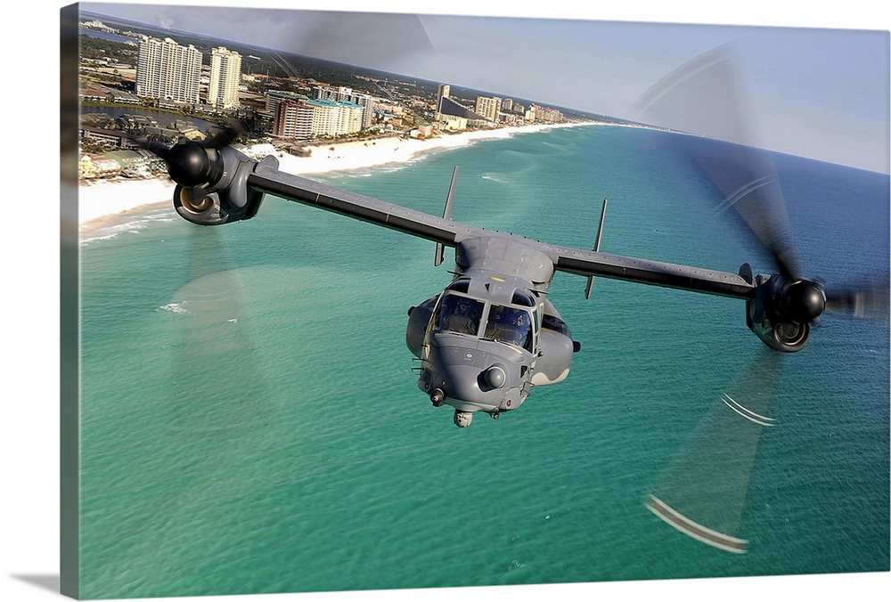 Large Gallery-Wrapped Canvas Wall Art Print 24 x 16 entitled A CV22 Osprey aircraft flies over Floridas Emerald Coast Gallery-Wrapped Canvas entitled A CV22 Osprey aircraft flies over Floridas Emerald Coast.  Large landscape photograph of a CV22 Osprey aircraft flying toward the camera over the green and blue waters of the Emerald Coast buildings along the beach in the background in Florida.  Multiple sizes available.  Primary colors within this image include Black White Teal Gray Blue.  Made in USA.  All products come with a 365 day workmanship guarantee.  Inks used are latex-based and designed to last.  Canvases have a UVB protection built in to protect against fading and moisture and are designed to last for over 100 years.  Canvas frames are built with farmed or reclaimed domestic pine or poplar wood.