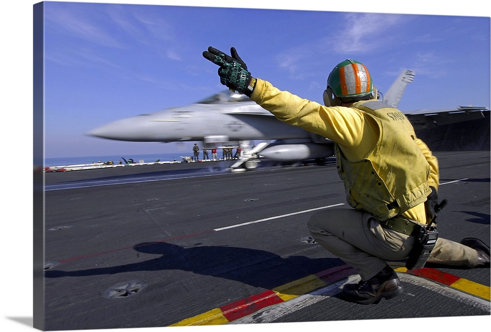 Large Solid-Faced Canvas Print Wall Art Print 36 x 24 entitled A shooter signals the launch of an F/A-18 Super Hornet Solid-Faced Canvas Print entitled A shooter signals the launch of an FA-18 Super Hornet.  Persian Gulf, February 7, 2008 - A shooter on the flight deck of the Nimitz-class aircraft carrier USS Harry S. Truman, gives the signal for an FA-18E Super Hornet to launch off ship. Truman and embarked Carrier Air Wing 3 are deployed supporting Operations Iraqi Freedom, Enduring Freedom and maritime security operations.  Multiple sizes available.  Primary colors within this image include Dark Red, Peach, Black, White.  Made in USA.  Satisfaction guaranteed.  Inks used are latex-based and designed to last.  Archival inks prevent fading and preserve as much fine detail as possible with no over-saturation or color shifting.  Canvas is handcrafted and made-to-order in the United States using high quality artist-grade canvas.