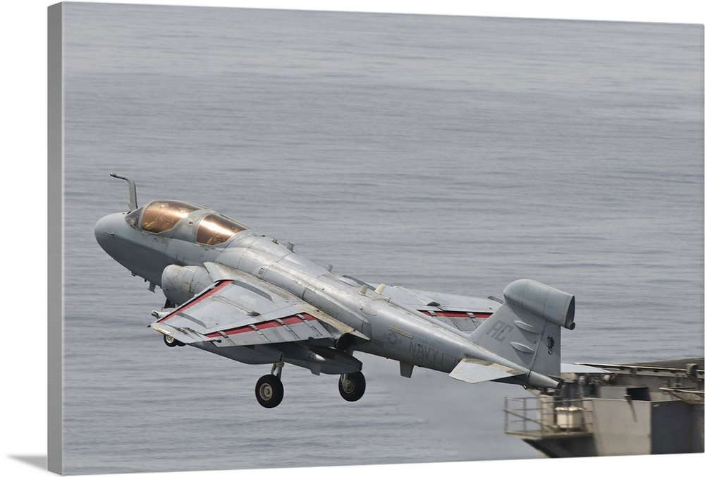 Large Solid-Faced Canvas Print Wall Art Print 36 x 24 entitled An EA-6B Prowler lifts off from the flight deck of USS Harr... Solid-Faced Canvas Print entitled An EA-6B Prowler lifts off from the flight deck of USS Harry S. Truman.  An EA-6B Prowler assigned to VAQ-130 lifts off from the flight deck of USS Harry S. Truman in support of Operation Enduring Freedom.  Multiple sizes available.  Primary colors within this image include Dark Gray, Light Gray.  Made in the USA.  All products come with a 365 day workmanship guarantee.  Inks used are latex-based and designed to last.  Canvas depth is 1.25 and includes a finished backing with pre-installed hanging hardware.  Canvas is handcrafted and made-to-order in the United States using high quality artist-grade canvas.