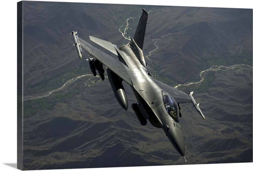 Large Solid-Faced Canvas Print Wall Art Print 36 x 24 entitled An F-16C Fighting Falcon flies over Afghanistan Solid-Faced Canvas Print entitled An F-16C Fighting Falcon flies over Afghanistan.  July 22, 2014 - An F-16C Fighting Falcon flies over Afghanistan after an in-air refueling mission in support of Operation Enduring Freedom.  Multiple sizes available.  Primary colors within this image include Gray, Silver.  Made in the USA.  All products come with a 365 day workmanship guarantee.  Inks used are latex-based and designed to last.  Canvas is handcrafted and made-to-order in the United States using high quality artist-grade canvas.  Archival inks prevent fading and preserve as much fine detail as possible with no over-saturation or color shifting.