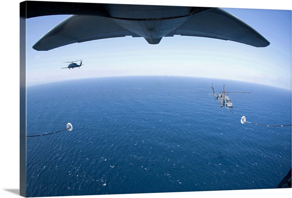 Large Solid-Faced Canvas Print Wall Art Print 30 x 20 entitled An MC-130P Combat Shadow prepares to refuel two HH-60G Pave... Solid-Faced Canvas Print entitled An MC-130P Combat Shadow prepares to refuel two HH-60G Pave Hawk helicopters.  March 18, 2011 - An MC-130P Combat Shadow crew prepares to refuel two HH-60G Pave Hawk helicopters above the Pacific Ocean.  Multiple sizes available.  Primary colors within this image include Black, Muted Blue, Pale Blue.  Made in USA.  All products come with a 365 day workmanship guarantee.  Inks used are latex-based and designed to last.  Archival inks prevent fading and preserve as much fine detail as possible with no over-saturation or color shifting.  Featuring a proprietary design, our canvases produce the tightest corners without any bubbles, ripples, or bumps and will not warp or sag over time.