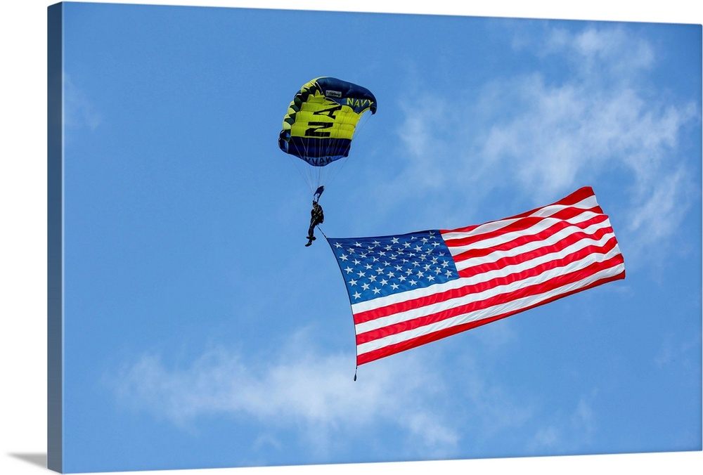 Large Gallery-Wrapped Canvas Wall Art Print 24 x 16 entitled Member of the U.S. Navy Parachute Team flies the American Flag Gallery-Wrapped Canvas entitled Member of the U.S. Navy Parachute Team flies the American Flag.  Member of the U.S. Navy Parachute Team flies the American Flag.  Multiple sizes available.  Primary colors within this image include Dark Red Sky Blue Black Lime Green.  Made in USA.  Satisfaction guaranteed.  Archival-quality UV-resistant inks.  Canvas frames are built with farmed or reclaimed domestic pine or poplar wood.  Canvases have a UVB protection built in to protect against fading and moisture and are designed to last for over 100 years.