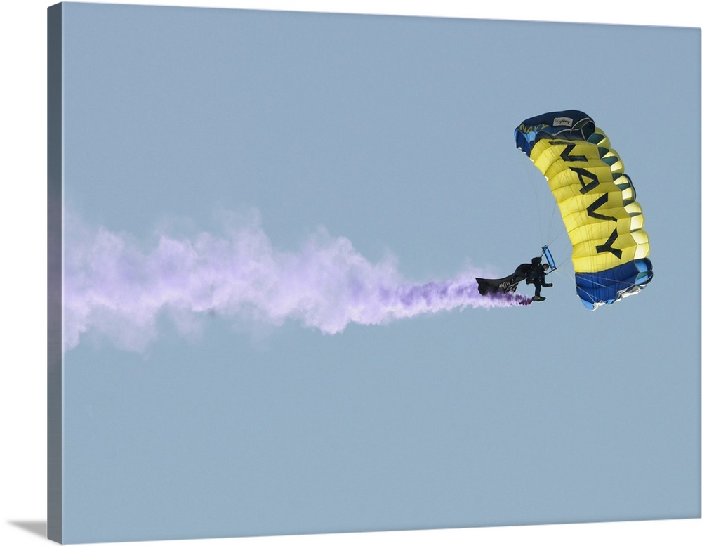 Large Gallery-Wrapped Canvas Wall Art Print 24 x 17 entitled Member of the US Navy parachute demonstration team Gallery-Wrapped Canvas entitled Member of the US Navy parachute demonstration team.  Member of the U.S. Navy parachute demonstration team.  Multiple sizes available.  Primary colors within this image include Dark Yellow White Muted Blue Light Gray Blue.  Made in USA.  All products come with a 365 day workmanship guarantee.  Inks used are latex-based and designed to last.  Canvas frames are built with farmed or reclaimed domestic pine or poplar wood.  Canvas is acid-free and 20 millimeters thick.