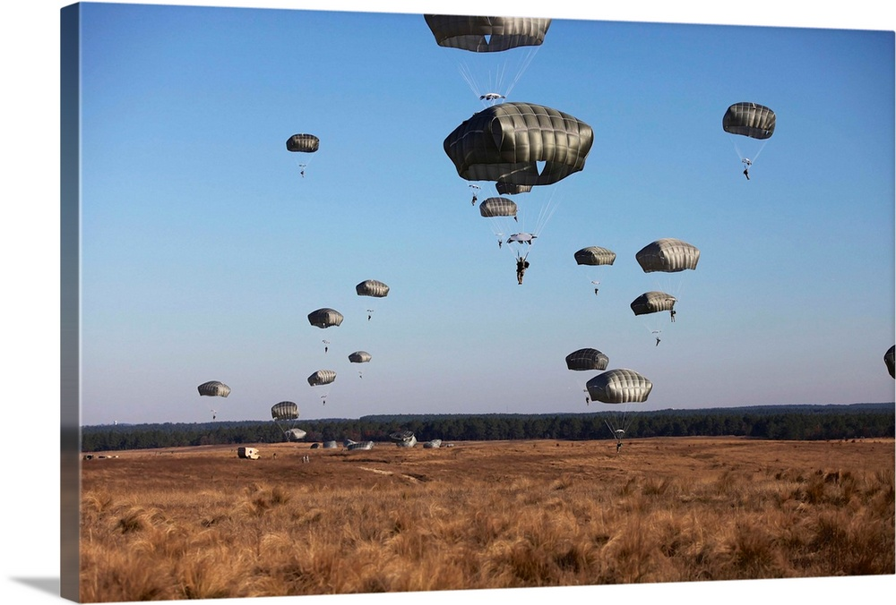 Large Solid-Faced Canvas Print Wall Art Print 30 x 20 entitled Paratroopers Fill The Sky For Operation Toy Drop At Fort Br... Solid-Faced Canvas Print entitled Paratroopers Fill The Sky For Operation Toy Drop At Fort Bragg, North Carolina.  Paratroopers fill the sky for Operation Toy Drop at Fort Bragg, North Carolina.  Multiple sizes available.  Primary colors within this image include Sky Blue, White, Dark Forest Green.  Made in USA.  All products come with a 365 day workmanship guarantee.  Archival-quality UV-resistant inks.  Archival inks prevent fading and preserve as much fine detail as possible with no over-saturation or color shifting.  Canvas depth is 1.25 and includes a finished backing with pre-installed hanging hardware.